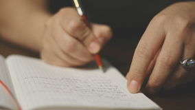 Unknown woman makes an entry in his notebook. Two hands opening a blank book. Close-up of woman's hands open notebook. Unknown woman makes an entry in his stock video footage