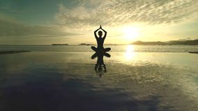 Unknown woman meditating on the beach stock photo