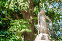 Unknown women mermaid sculpture on trees background in Milano city center park. Shiny summer day Stock Photo