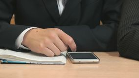 Unknown young man typing text using smartphone. Close-up of unknown young man in black suit sit at desk at lesson in the university and typing text using a black stock video