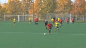 Unknowns athletes are playing football. Unknowns athletes in red and yellow uniform are playing football is not in focus stock video footage