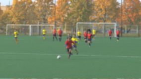 Unknowns athletes are playing football. Unknowns athletes in red and yellow uniform are playing football is not in focus slow motion stock footage