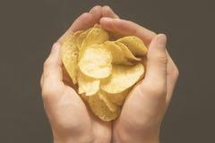 Unkosten der Handschale salzige Chips auf dunklem Hintergrund f halten stockfotografie