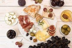 Unkosten der Käseplatte mit Stücken schimmeliger Käse, Prosciutto, p stockbild