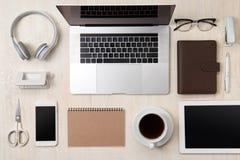 Unkosten des Bürotischs mit Notizbuch, Laptop, Kaffeetasse und s lizenzfreie stockfotografie