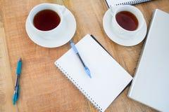 Unkosten des Kaffees und des Notizbuches auf dem Schreibtisch lizenzfreie stockbilder