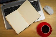 Unkosten des offenen Notizbuches auf Laptop stockfotografie