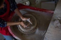 Unkosten des weiblichen Töpfers einen Lehm formend stockfoto