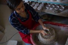 Unkosten des weiblichen Töpfers einen Lehm formend stockbilder