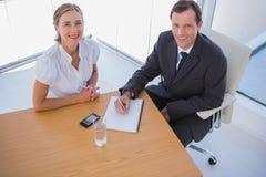 Unkosten von den lächelnden Geschäftsleuten, die Kenntnisse nehmen lizenzfreies stockfoto