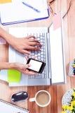 Unkosten von weiblichen Händen unter Verwendung des Laptops und des Smartphone Lizenzfreies Stockfoto