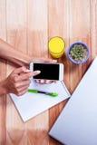 Unkosten von weiblichen Händen unter Verwendung des Smartphone stockbild