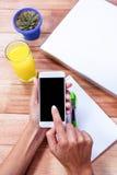 Unkosten von weiblichen Händen unter Verwendung des Smartphone lizenzfreie stockfotografie