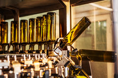 Unlabeled glass bottles in bottling machine at modern winery.  Stock Photo