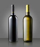Unlabelled red and white wine bottles on gray. Unlabelled corked full red and white wine bottles standing side by side on grey conceptual of a winery, wine Royalty Free Stock Photo