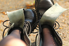 Unlaced black leather boots. Lit with autumn sun rays Stock Photography