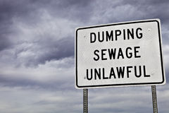 Unlawful Sewage Dumping Sign. Sign warns about dumping sewage royalty free stock photos