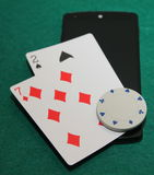 Unlcuky in online poker. Two cards - 7 and 2 - on mobile phone with white chip on them stock photography
