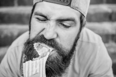 Unleashed appetite. Street food concept. Man bearded eat tasty sausage. Urban lifestyle nutrition. Carefree hipster eat. Junk food while sit stairs. Guy eating royalty free stock images