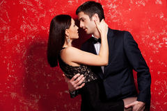 Unleashed desire. Beautiful young well-dressed couple hugging and looking at each other while standing against red background Stock Images