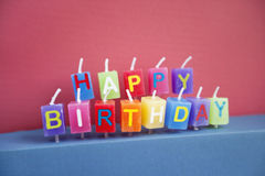 Unlit birthday candles over colored background Royalty Free Stock Images