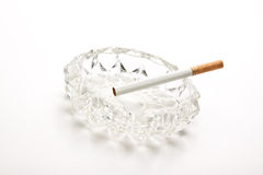 Unlit cigarette in glass ashtray Stock Image
