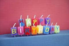 Unlit födelsedagstearinljus över kulör bakgrund Royaltyfria Bilder