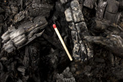 Unlit match stick laying on burnt coals Stock Image