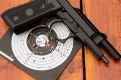 Unloaded air gun on target. On wooden table Royalty Free Stock Photography