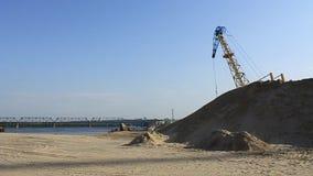 Unloading of barge. Big floating crane unload sand in river port stock video footage