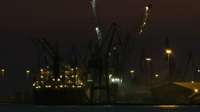 Unloading cargo ship at night 1. Night view of a harbour in a port with an illuminated cargo ship docked at the wharf being offloaded using cranes Shot on Canon stock video footage
