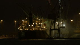 Unloading cargo ship at night 2. Night view of a harbour in a port with an illuminated cargo ship docked at the wharf being offloaded using cranes Shot on Canon stock video footage