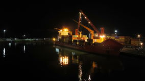 Unloading Cargo from a Ship in the Sea Port of Batumi by Night. Time Lapse. Cranes in seaport lift cargo containers on the ship and drop them to the pier stock footage