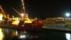 Unloading Cargo from a Ship in the Sea Port of Batumi by Night. Time Lapse. Cranes in seaport lift cargo containers on the ship and drop them to the pier. View stock footage