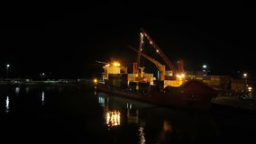 Unloading Cargo from a Ship in the Sea Port of Batumi by Night. Time Lapse. Cranes in seaport lift cargo containers on the ship and drop them to the pier. Full stock video