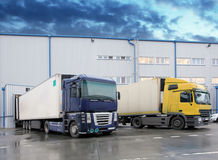 Unloading cargo truck at warehouse building Stock Image