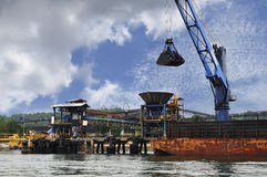 Unloading coal from barge to hopper Royalty Free Stock Images