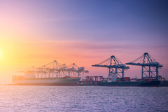 Unloading container shipping at cargo ship terminal., Twilight scene. Royalty Free Stock Photo
