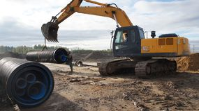 Unloading of corrugated pipes to the warehouse. Telescoping of pipes. Construction vehicles Stock Images
