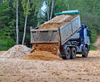 Unloading of a dump truck. Blue dump truck with  hoisted body unloads sand on the building site in rural areas Stock Photo