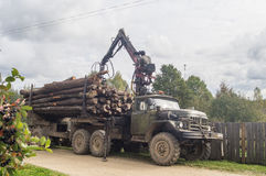 Unloading firewood from the truck in the Leningrad region of Russia. Royalty Free Stock Image