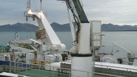Unloading of fish from the fishing trawler on the transport vessel. Norvegian sea stock footage