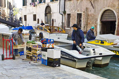 Unloading fruit and vegetables in Venice. Venice, Italy, Oct 24 2011: Water taxi and workboat navigating narrow canal in Venice.  All manner of supplies and Royalty Free Stock Images