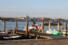 Unloading of goods from boats on the pier of Venice in the early morning royalty free stock image