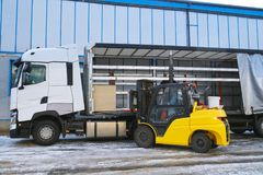 Unloading goods from a truck with a forklift. Transport royalty free stock photography