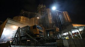 Unloading grain trucks at elevator on elevating hydraulic platform unloader at night. Grain crops transshipment at big. Unloading grain trucks at elevator on stock video