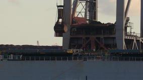 Unloading a huge coal ship. Crane lifting coal from huge bulk carrier ship stock video