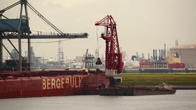 Unloading a huge ship. ROTTERDAM, THE NETHERLANDS -  SEPTEMBER 22, 2015: MS Berge Stahl being unloaded in the Port of Rotterdam. It used to be the largest iron stock video
