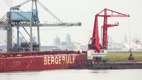 Unloading a huge ship. ROTTERDAM, THE NETHERLANDS - SEPTEMBER 22, 2015: MS Berge Stahl being unloaded in the Port of Rotterdam. It used to be the largest iron stock video footage
