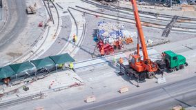 Unloading concrete plates from truck by crane at road construction site timelapse.